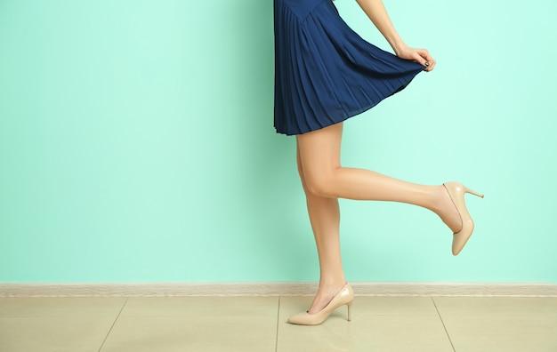 Jeune femme en chaussures élégantes près du mur de couleur