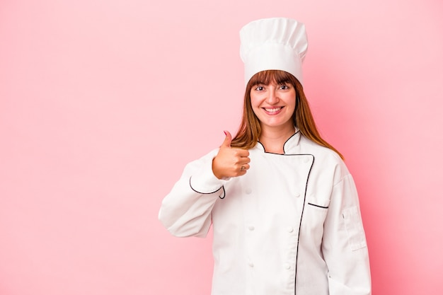 Jeune femme chef caucasienne isolée sur fond rose souriant et levant le pouce vers le haut