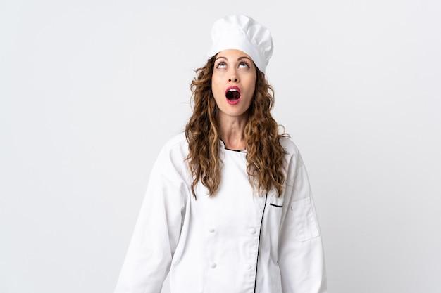 Jeune femme chef isolé sur fond blanc en levant et avec une expression surprise