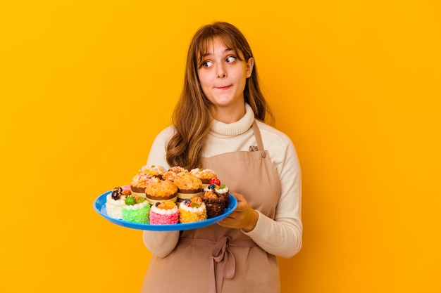 Jeune femme chef pâtissier isolée sur fond jaune confuse, se sent douteuse et incertaine.