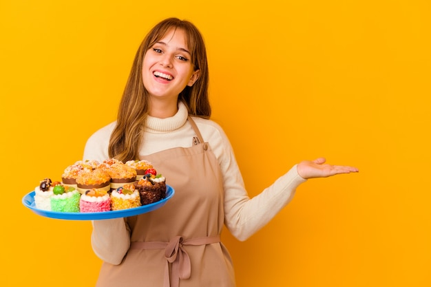 Jeune femme chef pâtissier isolée sur fond jaune montrant un espace de copie sur une paume et tenant une autre main sur la taille.