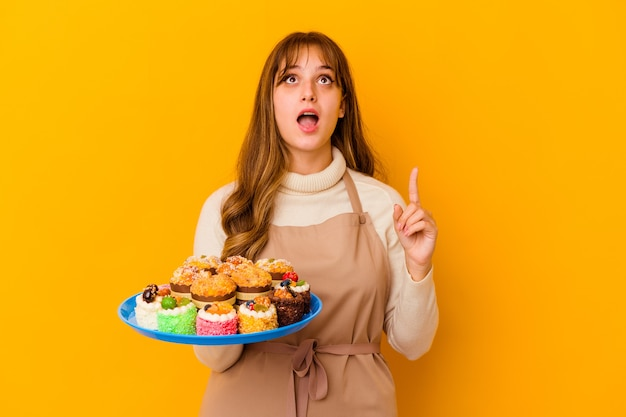 Jeune femme chef pâtissier isolée sur un mur jaune pointant vers le haut avec la bouche ouverte.