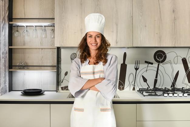 Jeune femme chef en toque et tablier debout avec les bras croisés dans une cuisine équipée moderne souriant à la caméra