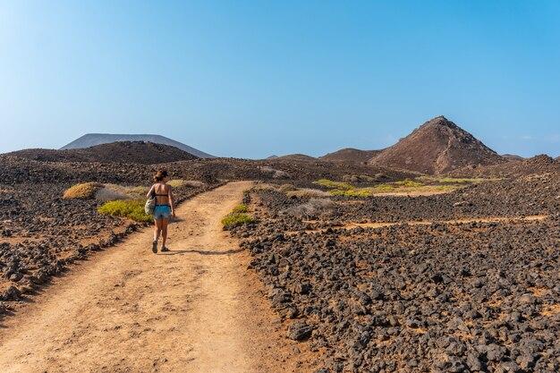 Une jeune femme sur le chemin au nord de l'isla de lobos, le long de la côte nord de l'île de fuerteventura, îles canaries. espagne