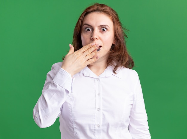 Jeune femme en chemise blanche à l'avant d'être choqué couvrant la bouche avec la main debout sur le mur vert