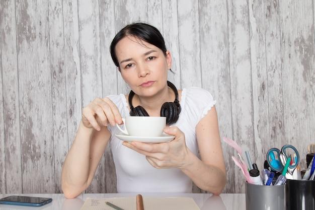 Jeune femme en chemise blanche, boire du café, écouter de la musique dans des écouteurs noirs, écrire des notes sur le mur gris