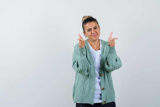Jeune femme en chemise blanche et cardigan vert menthe pointant vers la caméra avec l'index et l'air heureux