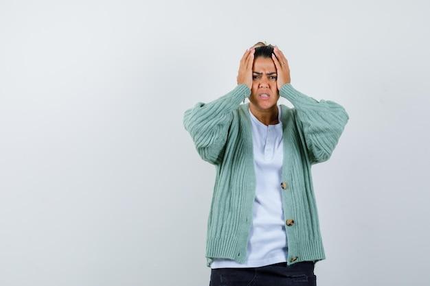 Jeune femme en chemise blanche et cardigan vert menthe se tenant la main à la tête et l'air ennuyé