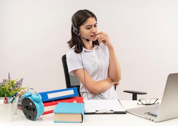 Jeune femme en chemise blanche et casque avec un microphone assis à la table avec des dossiers et un ordinateur portable en regardant son écran d'ordinateur confus sur un mur blanc