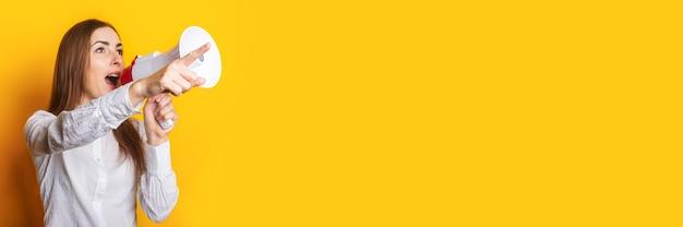 Une jeune femme en chemise blanche fait une annonce dans un mégaphone et pointe du doigt sur un fond jaune. concept d'embauche, aide recherchée. bannière.