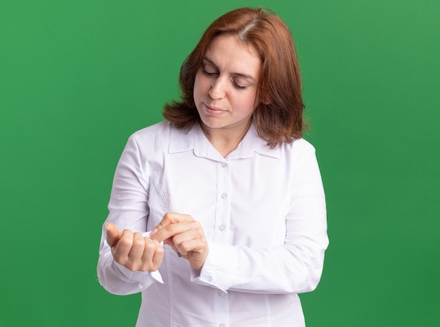 Jeune femme en chemise blanche fixant ses boutons de manchette à la confiance debout sur mur vert