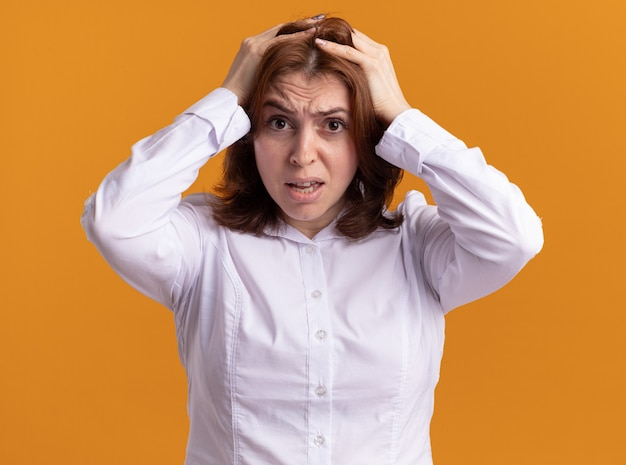 Jeune femme en chemise blanche lookign à l'avant confus et frustré avec les mains sur la tête pour erreur debout sur un mur orange