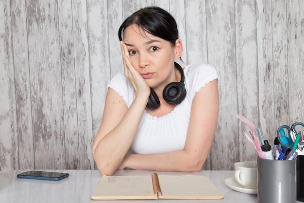 Jeune femme en chemise blanche montrant des émotions noir écouteurs sur mur gris