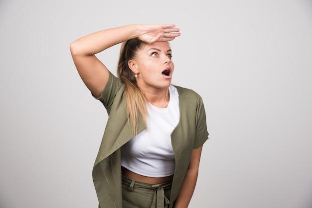 Jeune femme en chemise blanche à la recherche choquante.