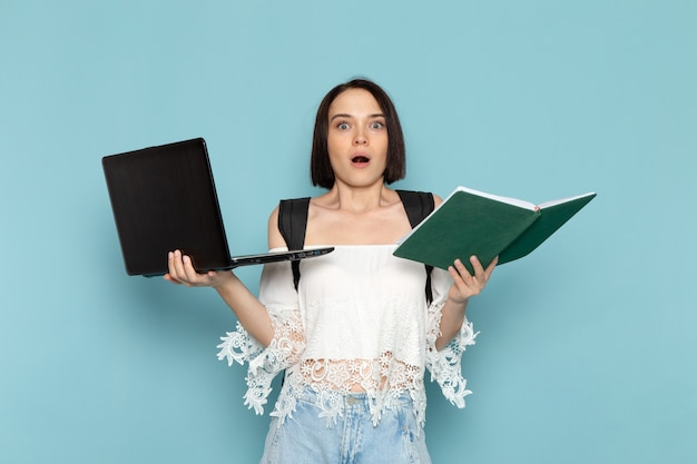 Jeune femme en chemise blanche et sac noir tenant un ordinateur portable et un cahier sur bleu