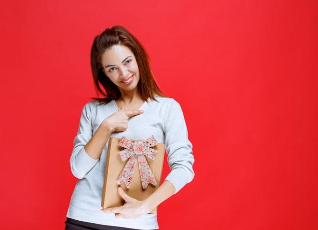 Jeune femme en chemise blanche tenant une boîte-cadeau en carton et montrant quelqu'un autour