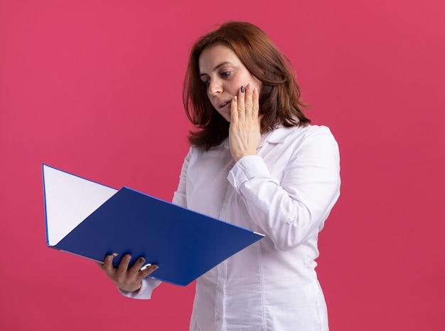 Jeune femme en chemise blanche tenant le dossier en le regardant avec une expression confuse debout sur un mur rose