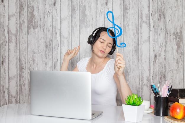 Jeune femme en chemise blanche tenant une note bleue en écoutant de la musique à travers des écouteurs noirs sur la table avec des stylos verts sur fond gris