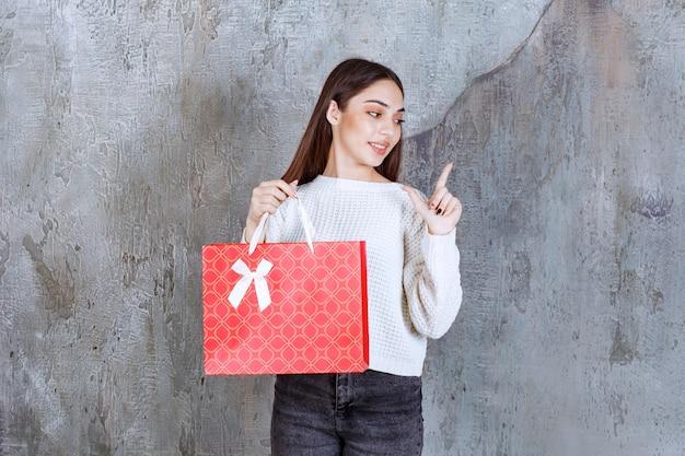 Jeune femme en chemise blanche tenant un sac rouge et a l'air confus et réfléchi