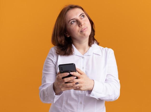 Jeune femme en chemise blanche tenant un smartphone à côté avec une expression pensive pensée positive debout sur un mur orange