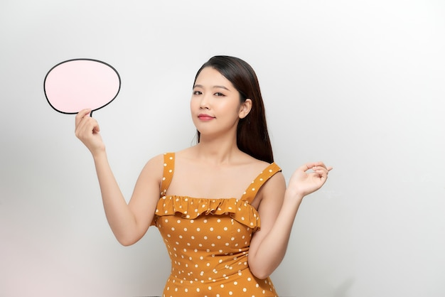Une jeune femme en chemise blanche tenant un symbole de boîte à pensées.