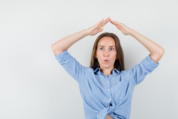 Jeune femme en chemise bleue faisant le geste du toit de la maison au-dessus de la tête et à la surprise