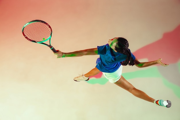Jeune femme en chemise bleue jouant au tennis. elle frappe la balle avec une raquette. prise de vue en intérieur avec une lumière mixte. jeunesse, flexibilité, puissance et énergie. vue de dessus.
