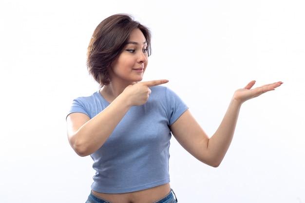 Jeune femme en chemise bleue montrant quelque chose de côté