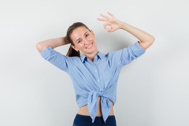 Jeune femme en chemise bleue, pantalon montrant signe ok tout en posant et à la joyeuse