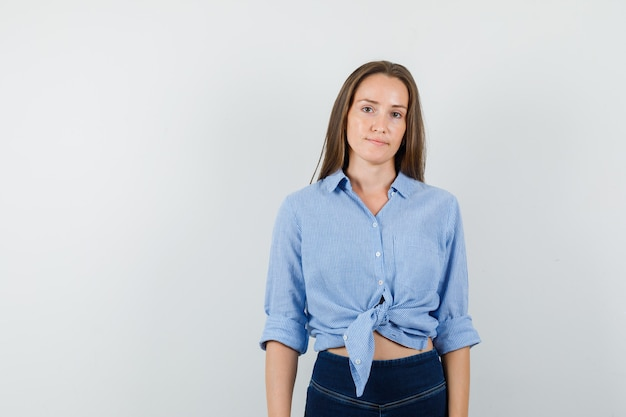 Jeune femme en chemise bleue, pantalon regardant la caméra et à la recherche sensible