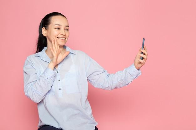 Jeune femme en chemise bleue posant à l'aide d'un téléphone sur le mur rose