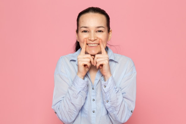 Jeune femme en chemise bleue posant sur le mur rose