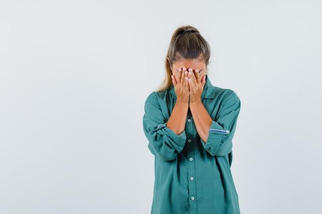 Jeune femme en chemise bleue, tenant les mains sur son visage et à la colère