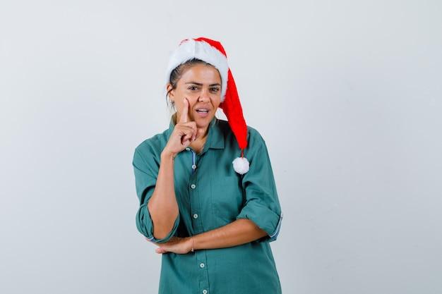 Jeune femme en chemise, bonnet de noel avec le doigt sur la joue et l'air confiant, vue de face.