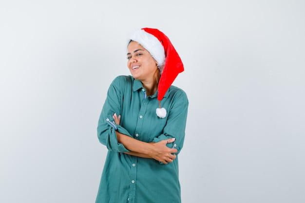Jeune femme en chemise, bonnet de noel avec les mains croisées et l'air joyeux, vue de face.