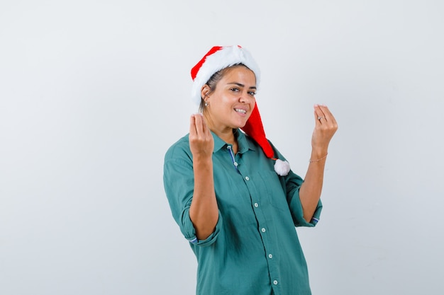 Jeune femme en chemise, bonnet de noel montrant le geste italien et l'air joyeux, vue de face.