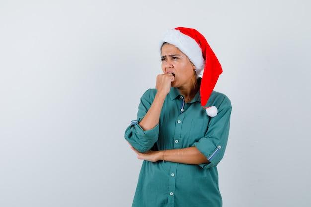 Jeune femme en chemise, bonnet de noel mordant le poing émotionnellement tout en détournant les yeux et l'air anxieux, vue de face.