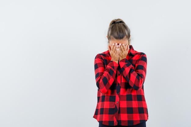 Jeune femme en chemise à carreaux couvrant le visage avec les mains et l'air déprimé