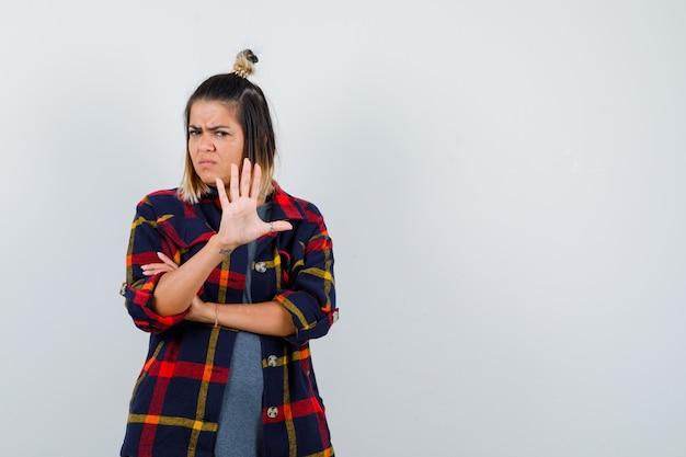 Jeune femme en chemise à carreaux décontractée montrant un geste d'arrêt et l'air lugubre, vue de face.