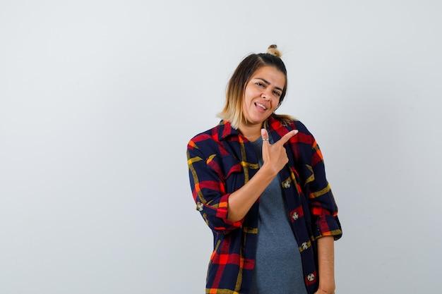 Jeune femme en chemise à carreaux décontractée pointant vers le haut et l'air heureux, vue de face.