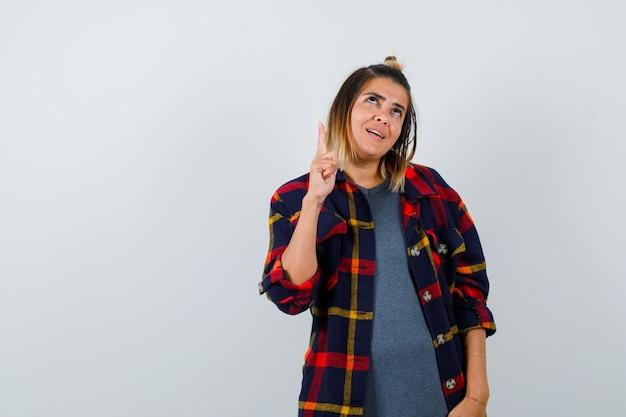 Jeune femme en chemise à carreaux décontractée pointant vers le haut et semblant attrayante, vue de face.