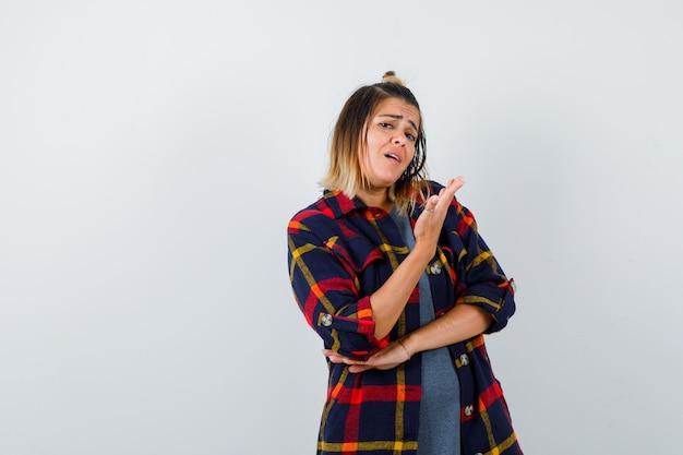 Jeune femme en chemise à carreaux décontractée tenant la paume devant le visage, debout sur le côté et l'air insatisfait.
