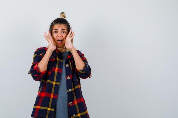 Jeune femme en chemise à carreaux décontractée tenant les paumes près de la bouche et l'air perplexe, vue de face.