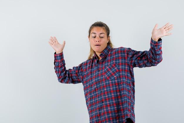 Jeune femme en chemise à carreaux, haussant les épaules et à la joie