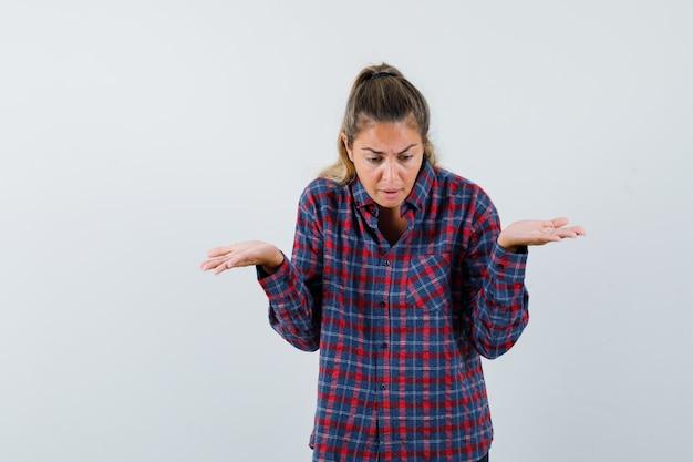 Jeune femme en chemise à carreaux haussant les épaules et à la perplexité