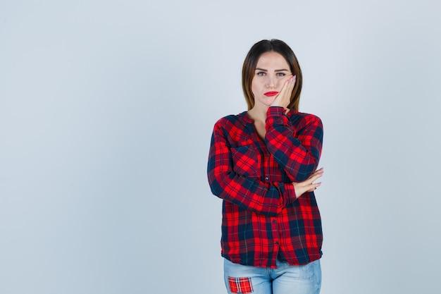 Jeune femme en chemise à carreaux, jeans appuyé sur la joue, pensant à quelque chose et l'air pensif, vue de face.