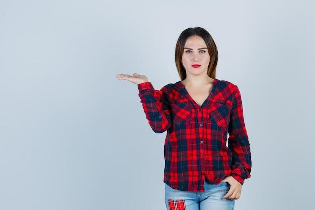 Jeune femme en chemise à carreaux, jeans étirant la main comme tenant quelque chose d'imaginaire, mettant la main dans la poche et ayant l'air sérieux, vue de face.