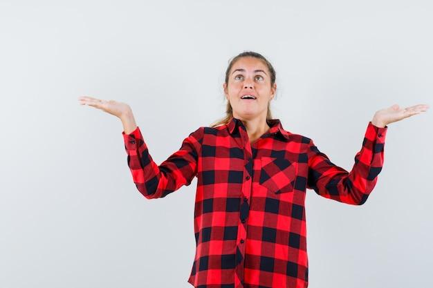 Jeune femme en chemise à carreaux en levant les bras tout en levant les yeux et à la reconnaissance
