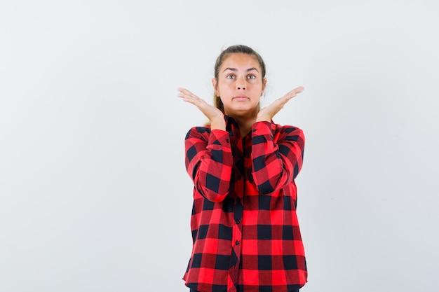 Jeune femme en chemise à carreaux en levant les mains tout en regardant vers le haut et à l'espoir, vue de face.