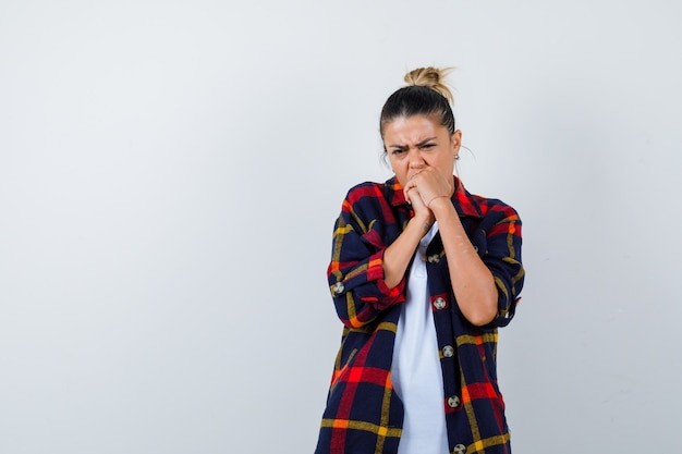 Jeune femme en chemise à carreaux avec les mains sur la bouche et à la perplexité, vue de face.